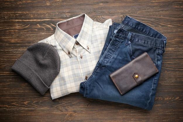 Niebieskie dżinsy, koszula, czapka i portfel na drewnianym stole, leżał na płasko. widok na casualowe stroje i dodatki. modny wygląd hipster.
