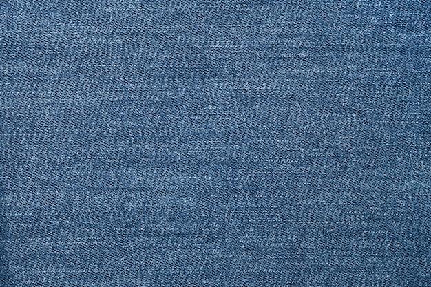 Niebieskie dżinsy, materiał o denimowej fakturze.