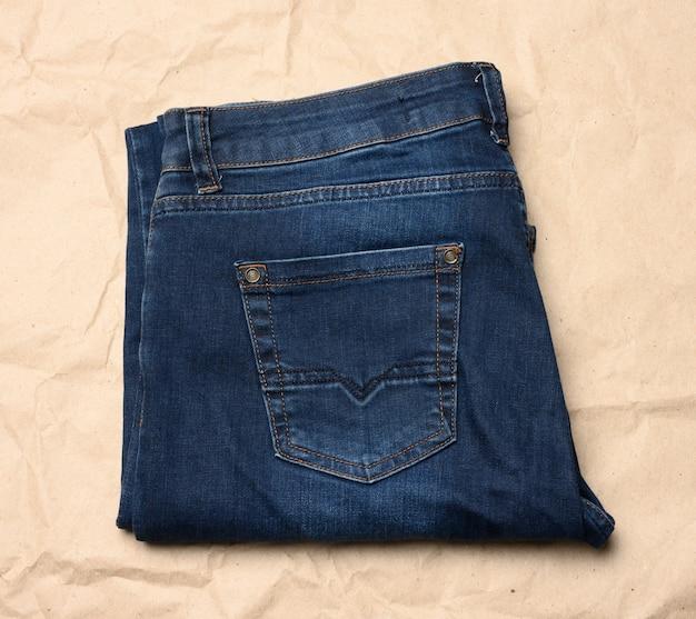 Niebieskie dżinsy męskie składane na brązowym papierze, widok z góry