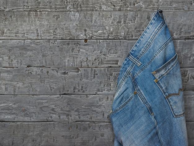 Niebieskie dżinsy męskie wiszące na drewnianej ścianie z szorstkich desek.
