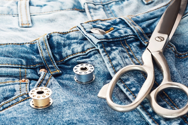 Niebieskie dżinsy, nożyczki, metalowe szpule z nitką z bliska. krawiectwo koncepcji odzieży casual denim. cięcie i szycie, tło. naturalne tkaniny jeansowe.