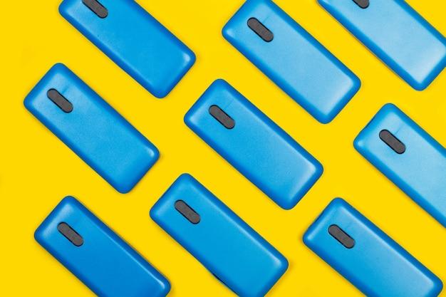 Niebieskie etui na smartfony na żółtym tle