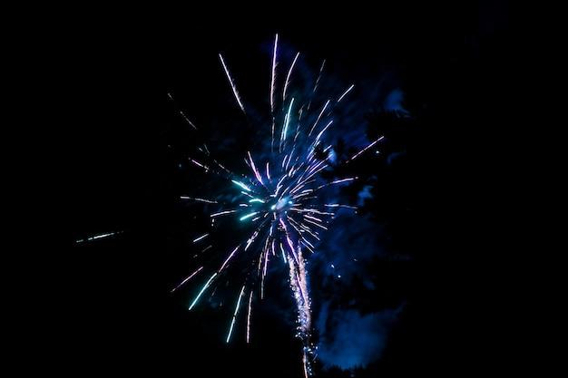 Niebieskie fajerwerki na ciemnym niebie. fajerwerki na cześć święta, nowy rok, boże narodzenie 2017. piękne duże fajerwerki na nocnym niebie