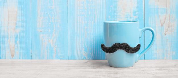 Niebieskie filiżanki z czarnymi wąsami na tle stół z drewna w godzinach porannych. dzień ojca i koncepcja międzynarodowego dnia mężczyzn