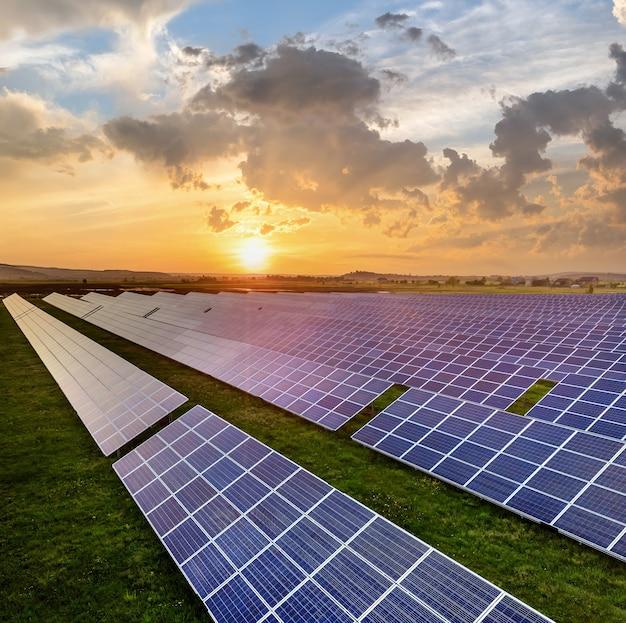 Niebieskie fotowoltaiczne panele słoneczne produkujące czystą energię odnawialną na wiejskim krajobrazie i tle zachodzącego słońca.