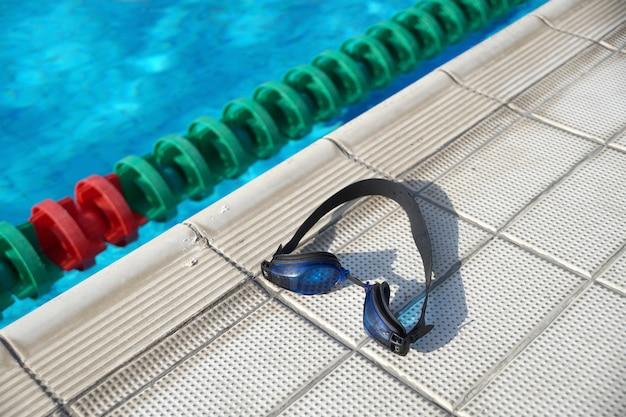 Niebieskie gogle do pływania na boku basenu
