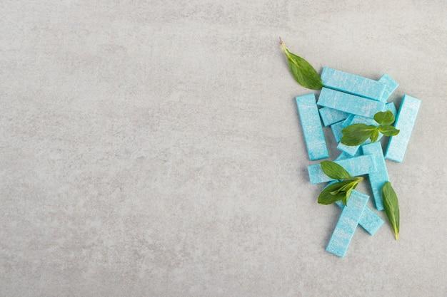 Niebieskie gumy do żucia z listkami mięty ułożone na kamiennym stole.