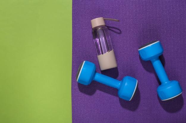Niebieskie hantle, butelka wody i mata fitness na zielonym backround z miejsca na kopię. koncepcja treningu.
