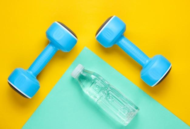 Niebieskie hantle i butelka wody