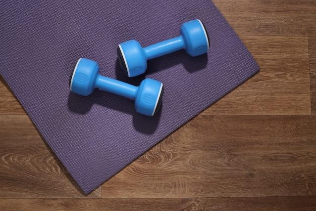 Niebieskie hantle i mata fitness na drewnianej podłodze. koncepcja treningu.