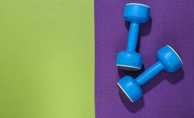 Niebieskie hantle i mata fitness na zielonym backround z miejsca na kopię. koncepcja treningu.