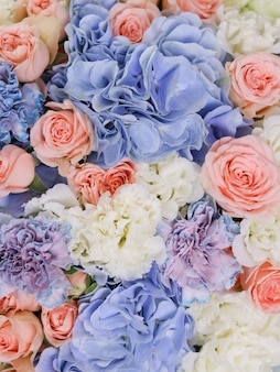 Niebieskie hortensje beżowe róże biała eustoma i niezwykłe goździki połączone w bukiecie