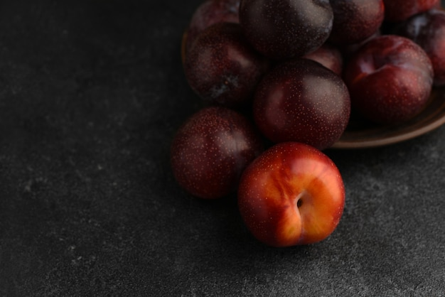 Niebieskie i czerwone gruszki w płycie ceramicznej na stole z ciemnego kamienia. czerwona śliwka na pierwszym planie. selektywne ustawianie ostrości.