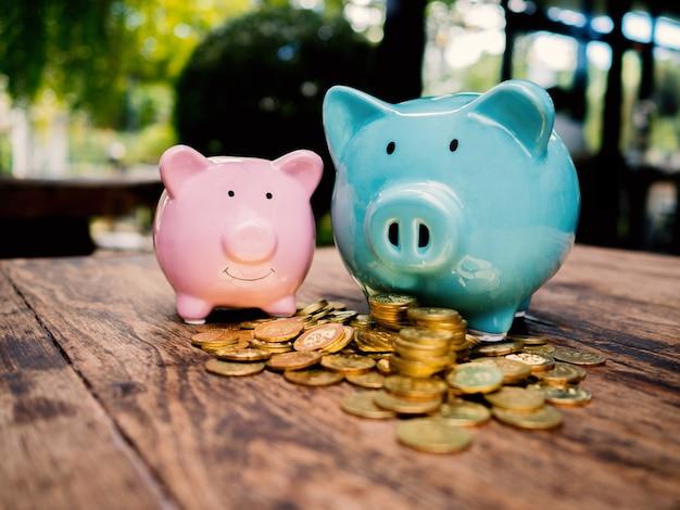 Niebieskie i różowe dwie skarbonki ze stosem złotych monet oszczędzanie pieniędzy na koncepcję funduszu emerytalnego