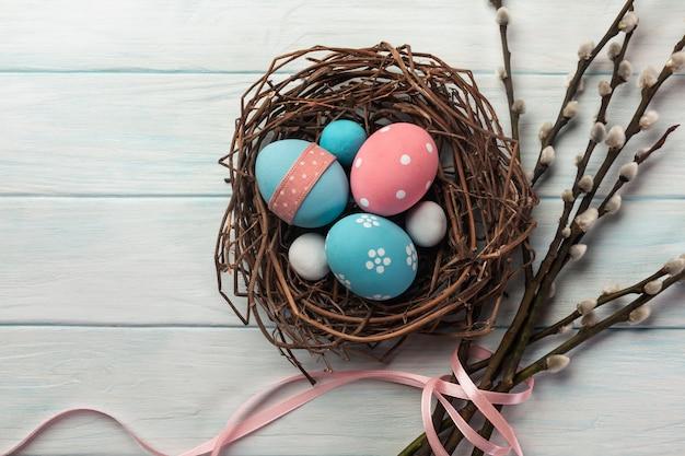Niebieskie i różowe kolorowe jajka w gnieździe i wierzba cipki. wielkanocna kartka z pozdrowieniami.