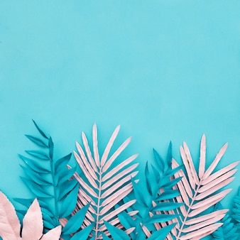 Niebieskie i różowe liście palmowe na niebieskim tle
