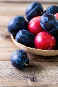 Niebieskie i różowe śliwki organiczne na ciemny drewniany.