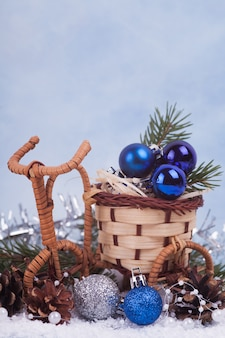 Niebieskie i srebrne bombki w wiklinowym garnku. ozdoby świąteczne