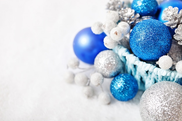 Niebieskie i srebrne świąteczne zabawki na jasnym tle.