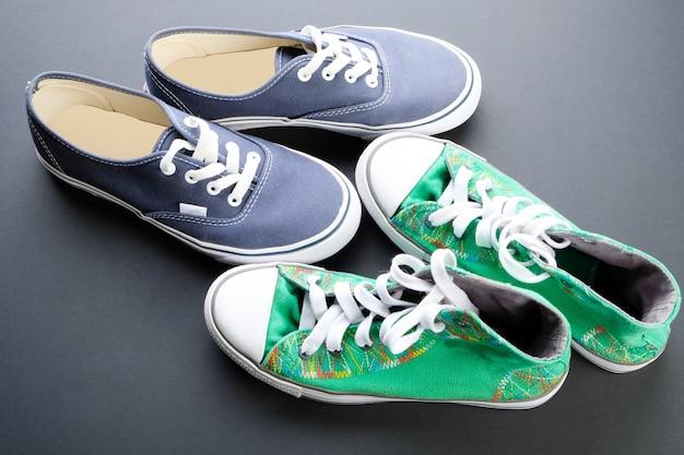 Niebieskie i zielone trampki na ciemnej podłodze