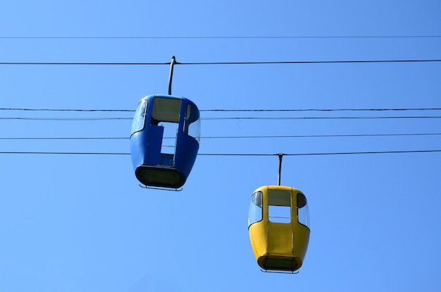 Niebieskie i żółte kabiny pasażerskie na jasnym niebie