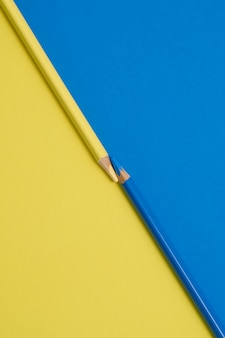 Niebieskie i żółte kolorowe kredki na żółtym i niebieskim stole