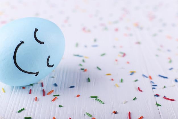 Niebieskie jajko z malowanymi uśmiechami wesołych świąt wielkanocnych kartkę z życzeniami.