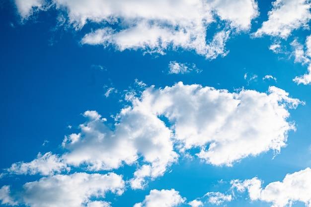 Niebieskie, jasne niebo z kilkoma chmurami i świecącym słońcem