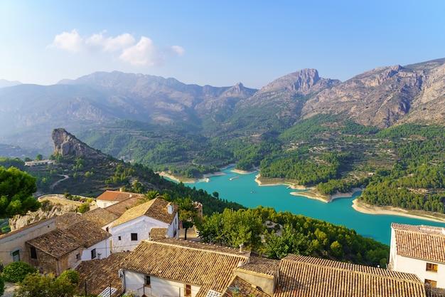 Niebieskie jezioro w dolinie i domy w górach w południowej hiszpanii. guadalest alicante.