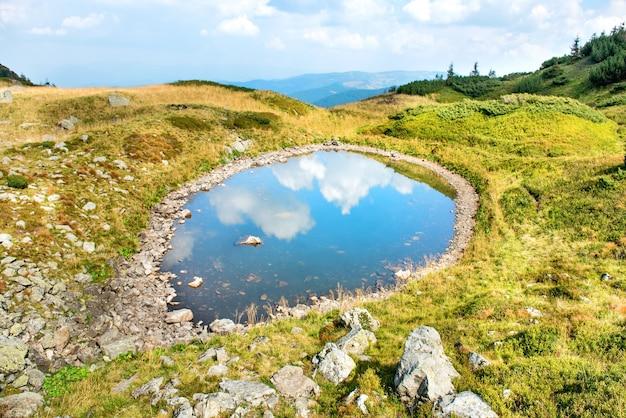 Niebieskie jezioro w górach z odbiciem białych chmur