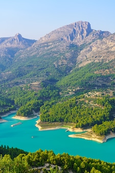 Niebieskie jezioro w zielonej dolinie obok wysokich gór skalistych. guadalest alicante.