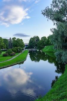 Niebieskie jezioro w zielonym parku odbijające niebo i chmury w wodzie.