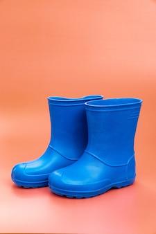 Niebieskie kalosze na różowym tle. buty na deszczową pogodę i kałuże. sklep z butami. chroń stopy przed wilgocią i brudem.