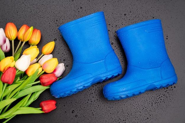 Niebieskie kalosze z wielokolorowymi tulipanami na czarnym tle. buty na deszczową pogodę i kałuże. sklep z butami. chroń stopy przed wilgocią i brudem.