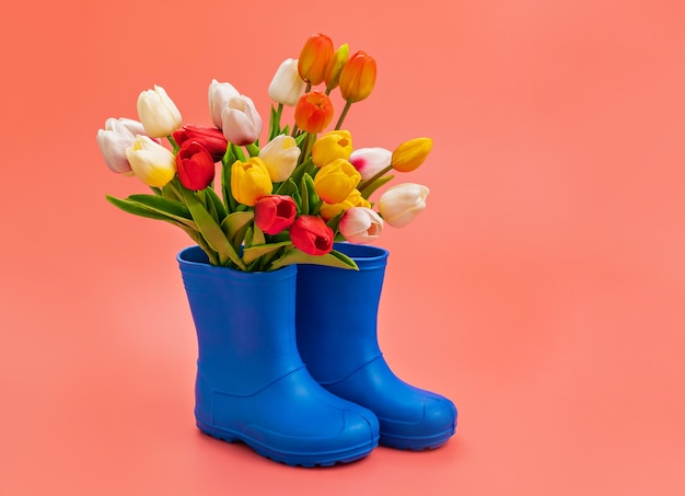 Niebieskie kalosze z wielokolorowymi tulipanami na różowym tle. buty na deszczową pogodę i kałuże. sklep z butami. chroń stopy przed wilgocią i brudem.