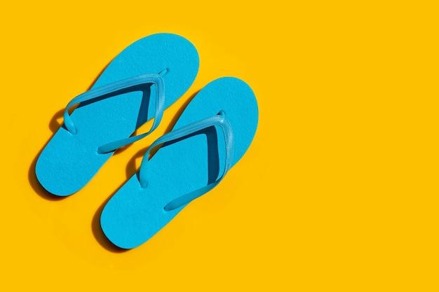 Niebieskie klapki na żółtym tle. ciesz się koncepcją letnich wakacji.