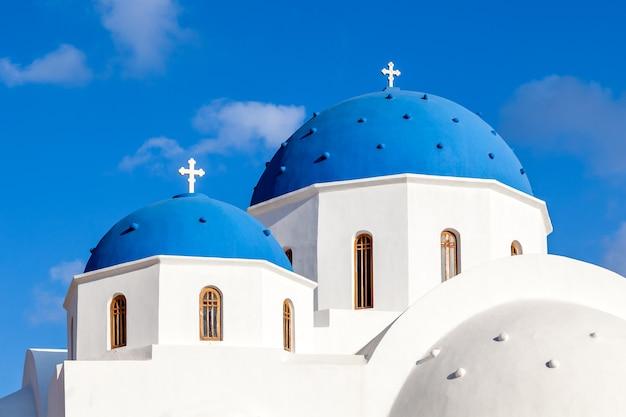 Niebieskie kopuły prawosławnego kościoła białego w perissa, wyspa santorini, grecja
