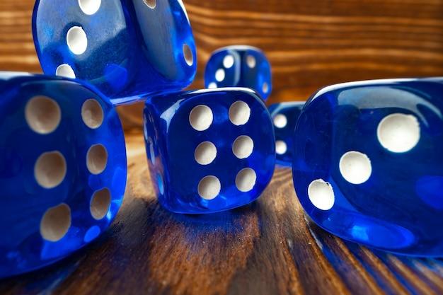 Niebieskie kostki do gry przeciwko brązowym drewnianym bliska