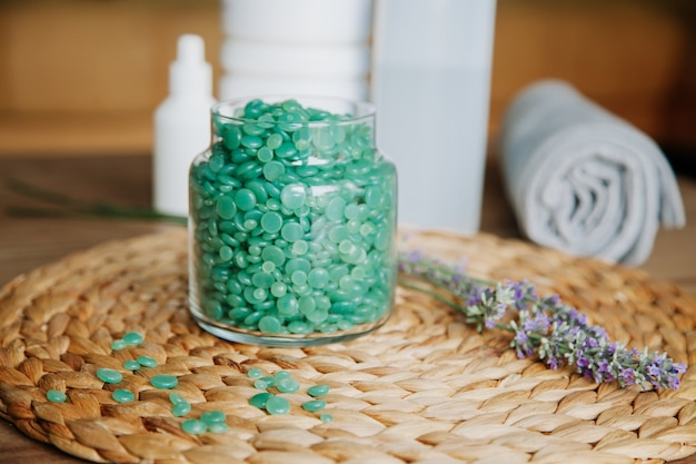 Niebieskie krople wosku pasty słodzącej w przezroczystym słoiku na drewnie