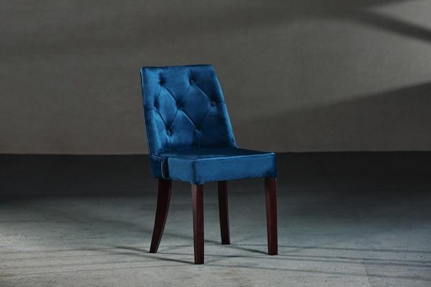 Niebieskie krzesło do jadalni w studio z szarymi ścianami