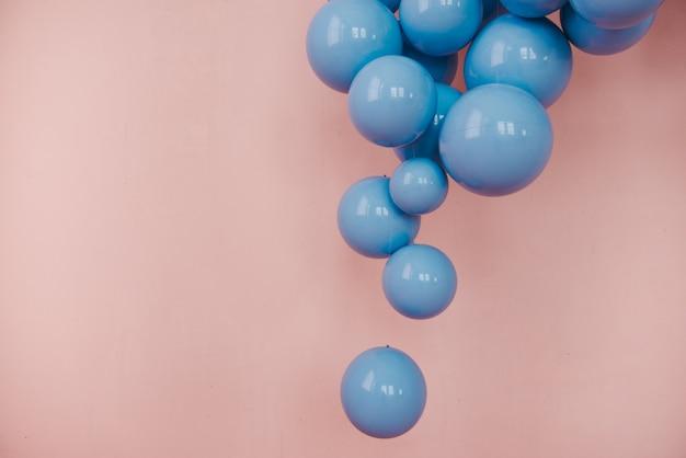Niebieskie kulki na różowym tle. dekoracja ślubna lub urodzinowa.