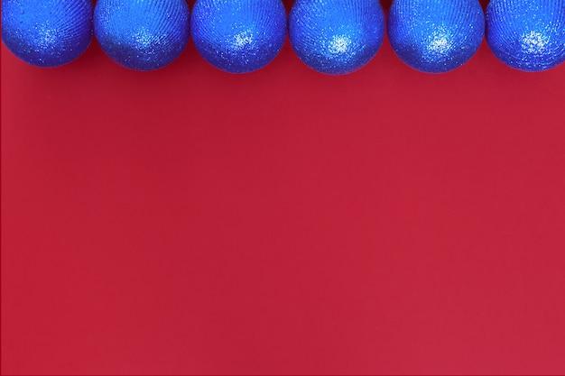 Niebieskie kulki święto bożego narodzenia błyszczące kulki na czerwonym tle papieru do wykorzystania jako dekoracja świąteczna powitanie tekstury.