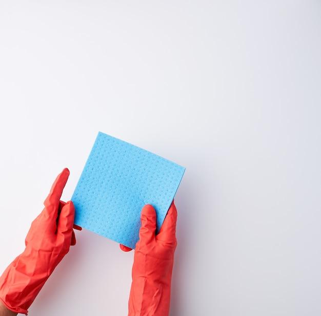 Niebieskie kwadratowe chłonne gąbki w dłoniach w czerwonych gumowych rękawiczkach