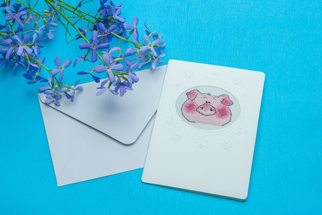 Niebieskie kwiaty i ręcznie robiona pocztówka z krzyżem w kopercie