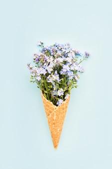 Niebieskie kwiaty niezapominajki w rożku lodów waflowych na jasnoniebieskim tle koncepcja lato widok z góry