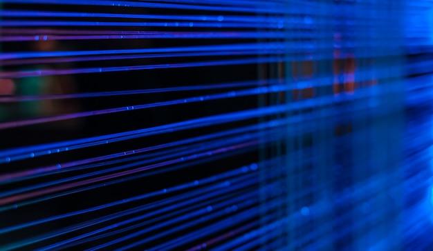 Niebieskie linie światła i kropki z przewodów światłowodowych na ciemnym tle, pomysł na komunikację komputerową, selektywne ustawianie ostrości, rozmycie, ciemne tło