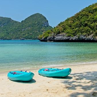 Niebieskie łodzie wiosłowe na plaży z pięknym oceanem w tle