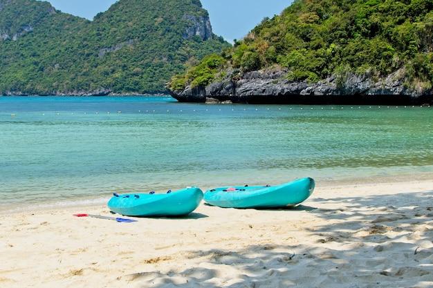 Niebieskie łodzie wiosłowe na plaży z pięknym oceanem w
