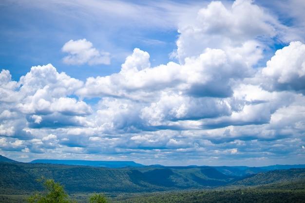Niebieskie niebo i biel chmurniejemy nad wzgórzami na jasnym niebie