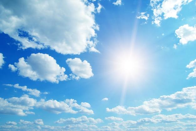 Niebieskie niebo z chmurami i słońcem